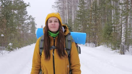 axe : Girl tourist in orange winter clothes walking along a winter forest road with a backpack on her shoulders. It is snowing outside. Slow motion. Vidéos Libres De Droits
