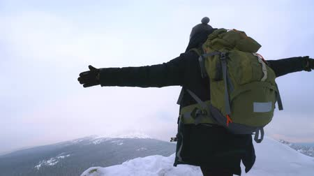 admires : A young man, a tourist with a backpack, stands on the edge of the mountain next to the cliff, arms outstretched to the side, and admires the view of the top of the mountain. Winter season. Stock Footage