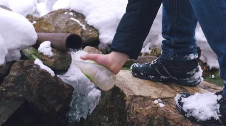 sede : A tourist pours water from a mountain spring into a plastic bottle. Winter time. Slow motion.