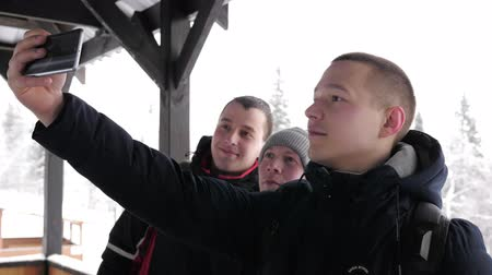 takes : A company of young tourists takes a selfie on a mobile phone in a natural park in winter. Slow motion.