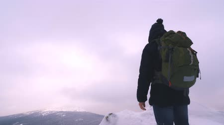 admires : A young man, a tourist with a backpack, stands on the edge of a mountain next to a cliff and admires the top of a mountain. Winter season. Slow motion.