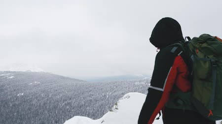 volgende : A young man, a tourist with a backpack, stands on the edge of the mountain next to the cliff, arms outstretched to the side, and admires the view of the top of the mountain. Winter season. Stockvideo