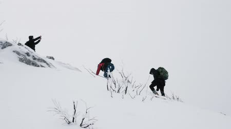 admires : A group of young people, tourists, with backpacks on their shoulders rises to the top of a snow-covered mountain. Slow motion. Stock Footage