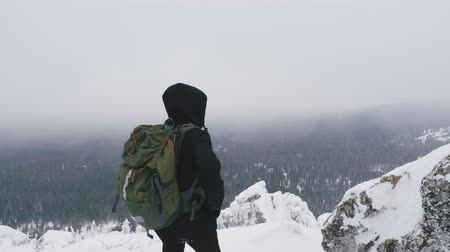 admires : A young man, a tourist, with a backpack on his shoulders, stands on top of a snow-covered mountain and admires the landscape. Slow motion.