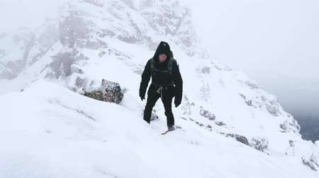 proximo : A young man, a tourist, with a backpack on his shoulders rises to the top of a snow-covered mountain. Slow motion. Archivo de Video