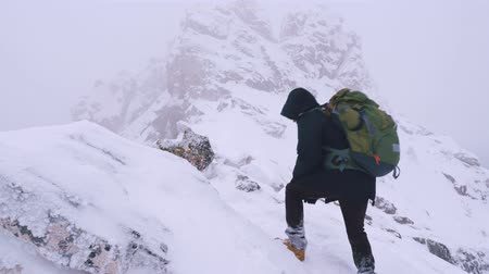 admires : A young man, a tourist, with a backpack on his shoulders rises to the top of a snow-covered mountain. Slow motion. Stock Footage