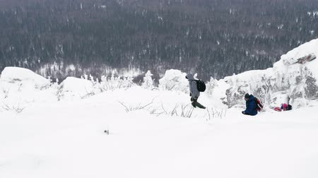 admires : A group of tourists with backpacks on their shoulders rises to the top of a snow-covered mountain. Slow motion.