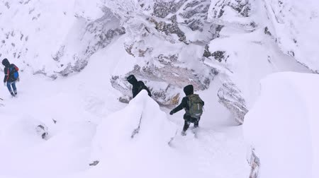 aşınmış kaya parçası : A group of tourists with backpacks on their shoulders descends from the top of a snow-covered mountain. Slow motion.