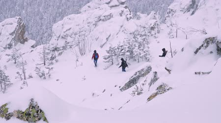 boulder rock : A group of tourists with backpacks on their shoulders descends from the top of a snow-covered mountain. Slow motion.