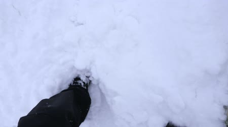 goes : A male tourist walks along the deep snow of a mountain path along a dangerous cliff. Close view of the legs. Slow motion.