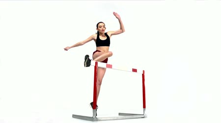 sportowiec : Young female athlete jumping over hurdle shooting with high speed camera, phantom flex.