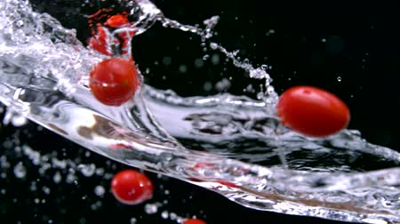 tomate cereja : Slo-motion cherry tomatoes mixing with water Stock Footage
