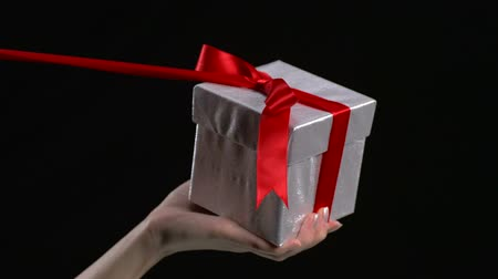 quantidade ínfima : Slo-motion red ribbon unwrapped from present