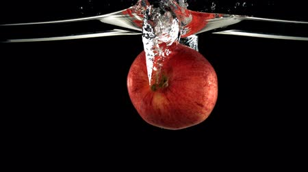 czerwone tło : Slo-motion red apple falling into water