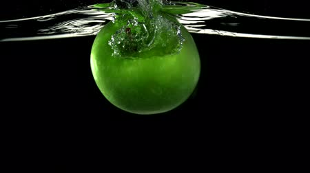 jabłka : Slo-motion green apple falling into water