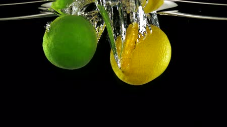 calcário : Slo-motion whole lemon and lime falling on water