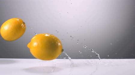 limão : Slo-motion whole lemons falling on water Stock Footage