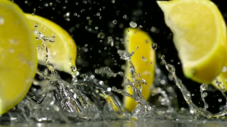 limão : Slo-motion lemon falling into wedges against black drop Stock Footage