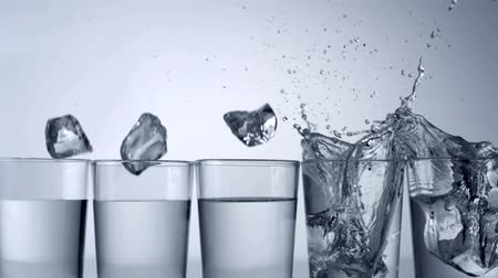 slomo : Slo-motion ice cubes falling into row of glasses, one misses