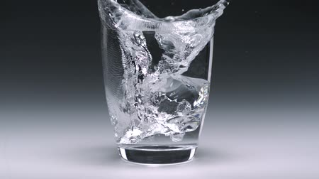 movements : Ice cube being tossed in glass of water shooting with high speed camera. Stock Footage