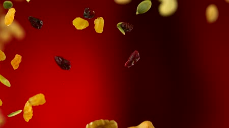 orzechy : nut and seed falling in the air on red background shooting with high speed camera.