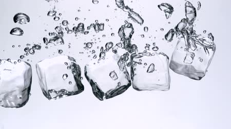 küpleri : Ice cubes falling in water on white background shooting with high speed camera.