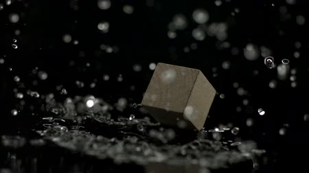 blocos : wooden block falling and spinning on water and making splash shooting with high speed camera.