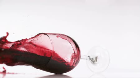 kiloccsantás : Glass of red wine falling and wine spilling over shooting with high speed camera. Stock mozgókép