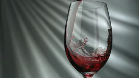 kırmızı şarap : Pouring red wine into glass in front of white fabric  shooting with a high speed camera. Stok Video