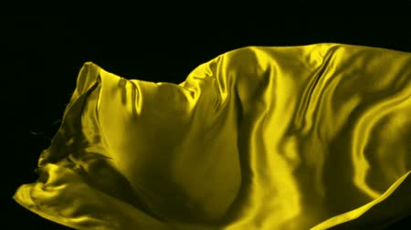 hedvábí : Yellow silk fabric flying in the air shooting with a high speed camera.