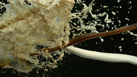 laktózy : Pouring coffee  milk and making splashes on black background shooting with high speed camera, phantom flex.