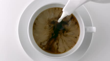 feketés csésze : Pouring milk into a cup of coffee shooting with high speed camera, phantom flex. Stock mozgókép