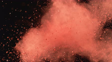 Red powderparticles fly after being exploded against black background. Shot with high speed camera, phantom flex 4K. 4K 30fps. Slow Motion. Стоковые видеозаписи