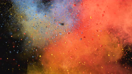Red, yellow and blue powderparticles fly after being exploded against black background. Shot with high speed camera, phantom flex 4K. 4K 30fps. Slow Motion.