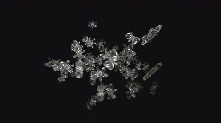 Camera follows snow flake crystals flying after being exploded against black background. Shot with high speed camera, phantom flex 4K.  Slow Motion. Unedited version is included at the end of clip.