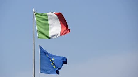 birleşik : the flags of Italy and the European Union on wind