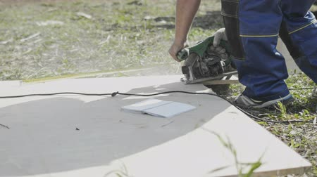 karbantartás : man cuts sheet of  plywood at the construction site