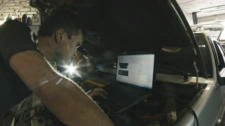diagnostics : Car service, computer diagnostics: mechanic repairs the damage using the pc in car service Stock Footage