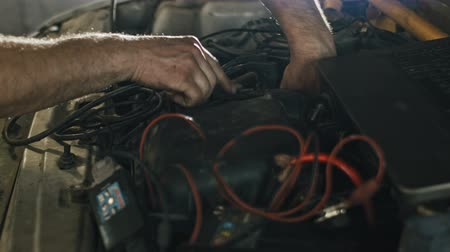 diagnostics : Car service, computer diagnostics: mechanic repairs the damage using the pc in car service, slider, close up Stock Footage