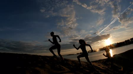 életerő : A group of athletes - two girls and a guy are fleeing the mountain, near river at dusk, slow-motion, silhouette