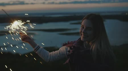 Новый год : Beautiful young woman stands on a high hill with sparkler at sunset in slow motion Стоковые видеозаписи
