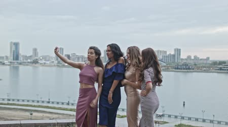 juntar : Four Attractive young women in party dresses on high hill get a selfie, wide shot Stock Footage