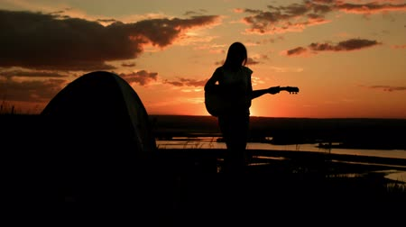 sátor : Attractive romantic girl playing the acoustic guitar, at sunset near camping on high hill, silhouette Stock mozgókép