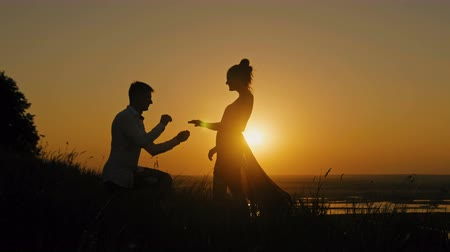 ma : Romantic Silhouette of Man Getting Down on his Knee and Proposing to Woman on high hill - Couple Gets Engaged at Sunset - Man Putting Ring on Girls Finger, slider shot
