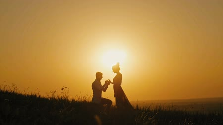 ma : Romantic Silhouette of Man Getting Down on his Knee and Proposing to Woman on high hill - Couple Gets Engaged at Sunset - Man Putting Ring on Girls Finger, slow motion Stock mozgókép