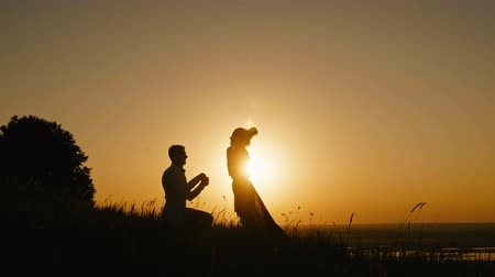 ma : Romantic Silhouette of Man Getting Down on his Knee and Proposing to Woman on high hill - Couple Gets Engaged at Sunset - Man Putting Ring on Girls Finger Stock mozgókép