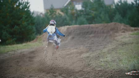 pista de corridas : Slow motion: Motocross racer jumping. Rear view of biker on track in rapid shoot