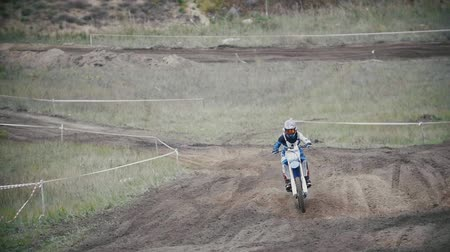 enduro : Motocross rider in a red jumpsuit chasing racer mxgirl on dirt bike on track in rapid shoot, Slow motion, close up