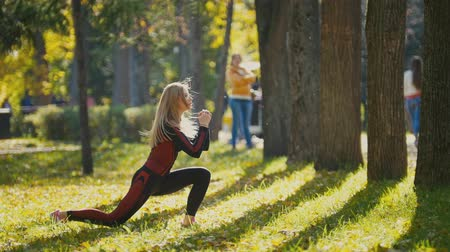 колготки : Fitness woman strength training doing workout at sunny autumn park. Fit caucasian sporty girl exercising her body - doing squats, side view