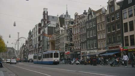 hármas : AMSTERDAM, NETHERLANDS - 16 oct 2016, tourists on the street, bicycle and cars - The tram rides through the historic center Stock mozgókép